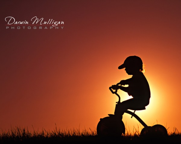 Child on a trike, silhoutte, sunset in background