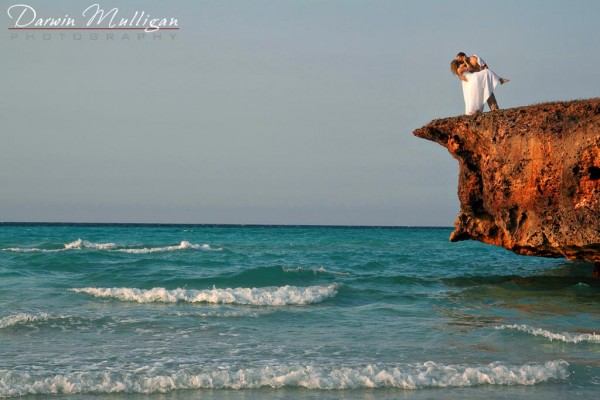 Destination wedding, bride and groom on a cliff overlooking the waves roll in on the beach