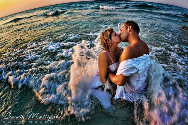 Destination wedding, newlywed couple in ocean with waves