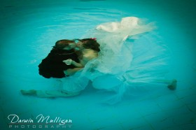 bride and groom completely submerged in a trash the dress session