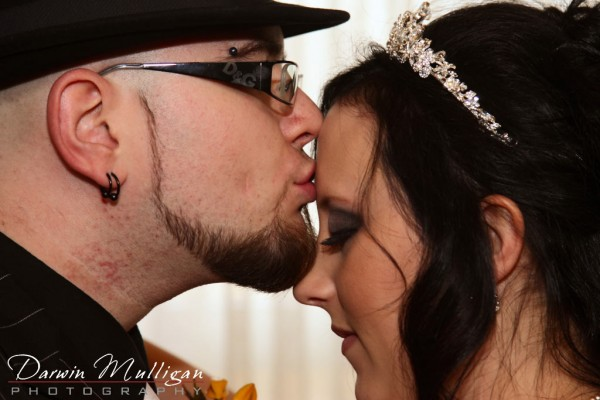 Mark kisses Christal on the forehead at their Edmonton wedding ceremony
